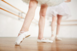 Faceless girls leg in ballet shoes making position on parquet with ballerina on background