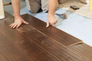 14202735 - man installing new laminate wood flooring abstract.